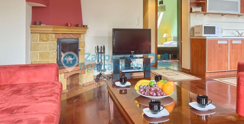 salon z tv i kominkiem w apartamencie w Zakopanem