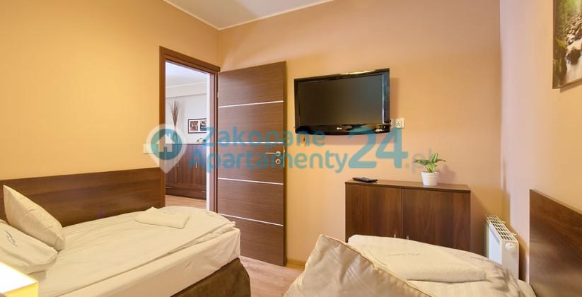dwa-łozka w sypialni w apartamencie